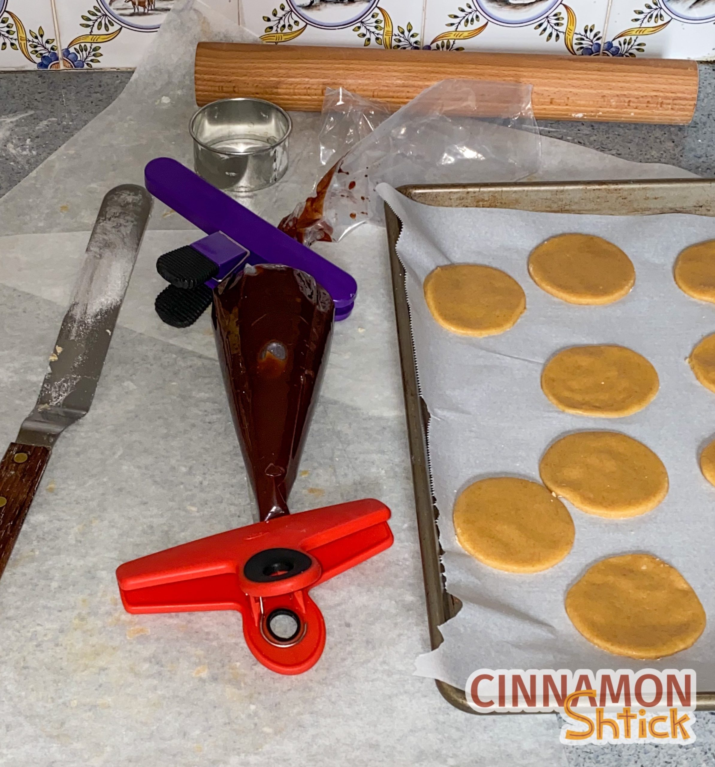 Hamantaschen dough cut in circles with brownie batter in piping bag