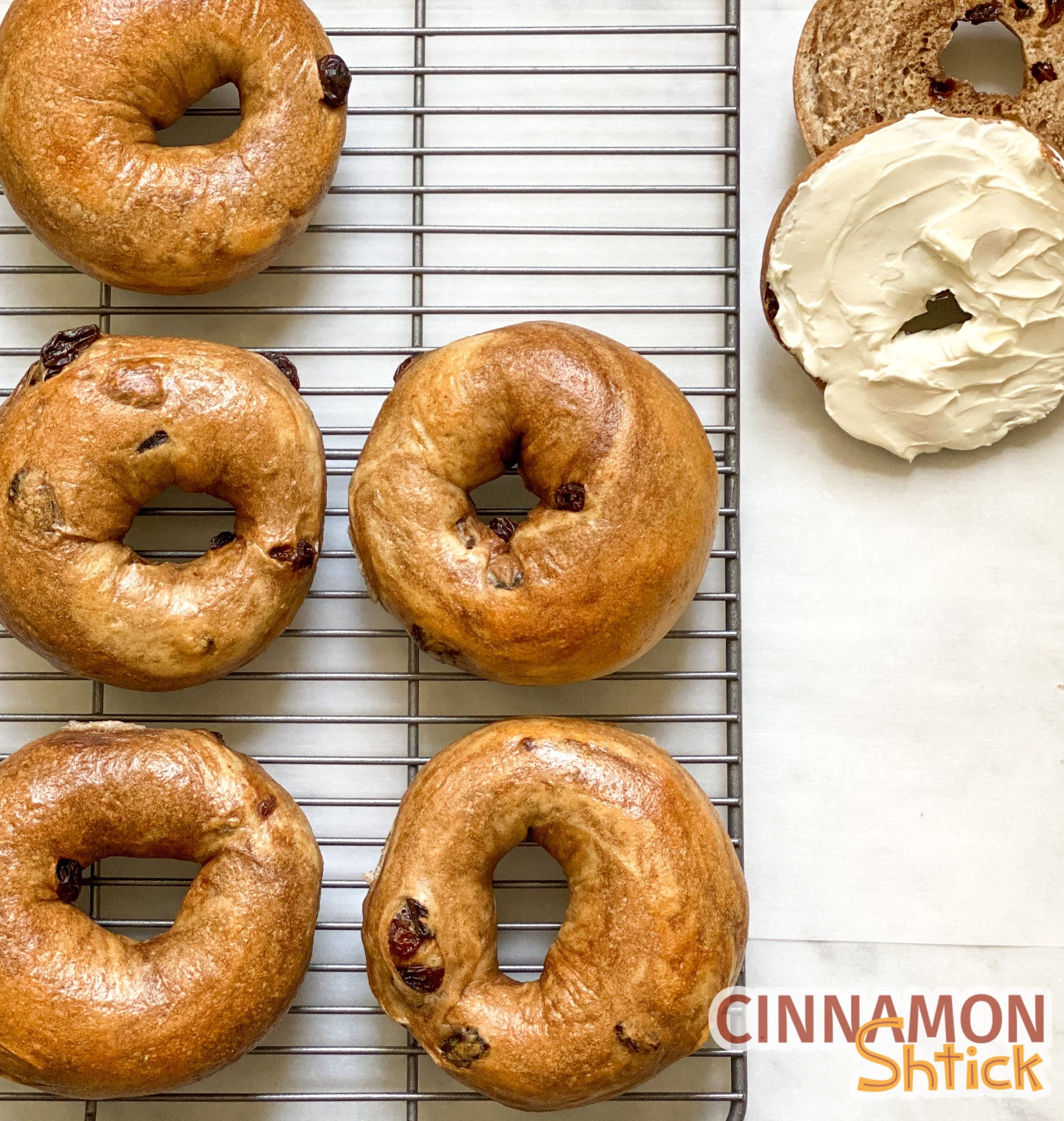 bagels on cooling rack with one cut in half with cream cheese on one side