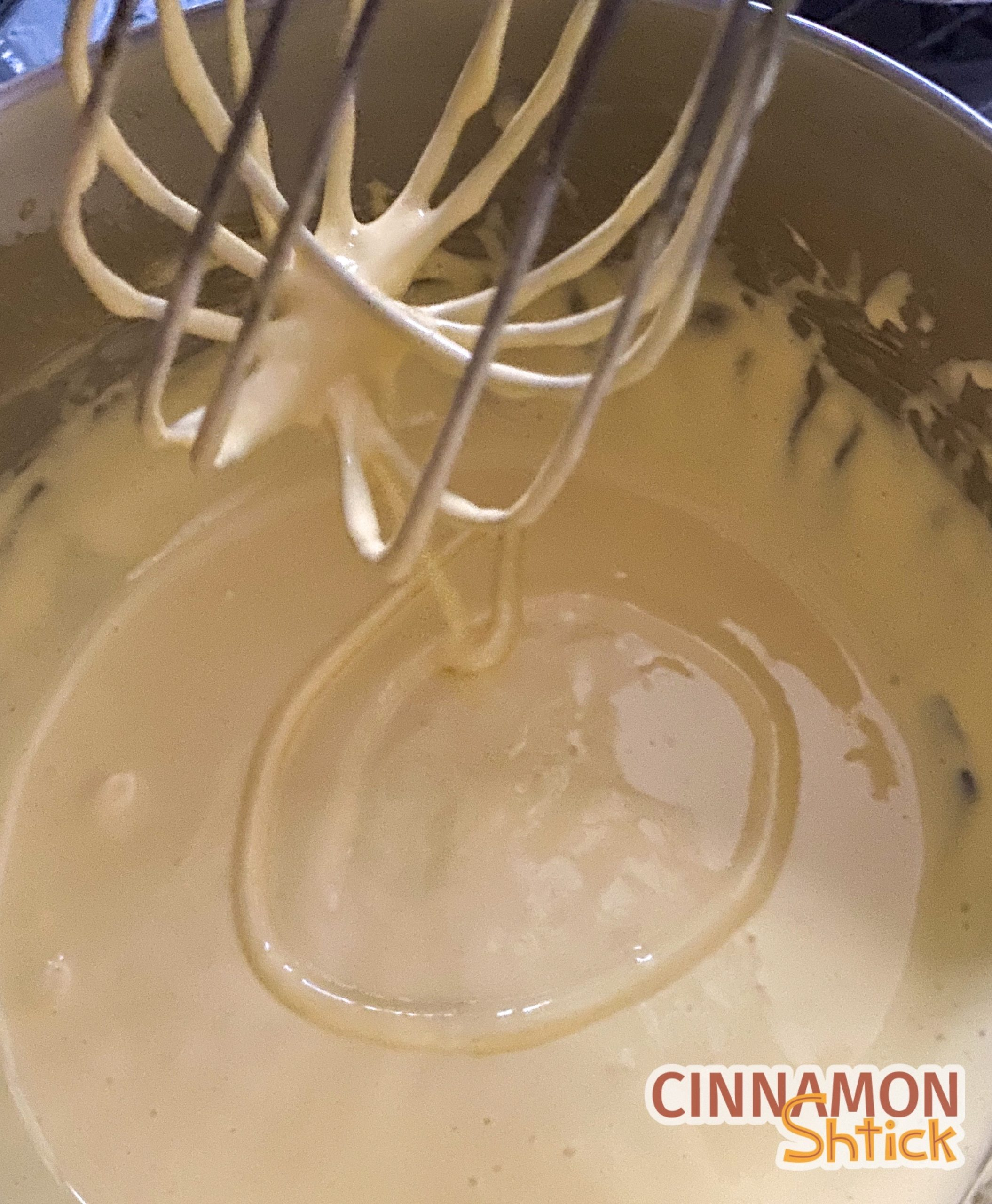 yoks and sugar whisked in bowl with whisk above showing ribbon of mixture in bowl