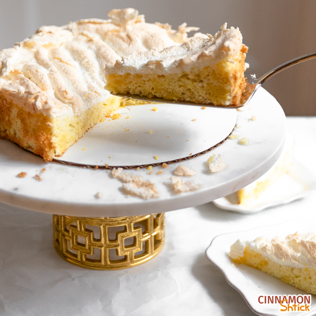 Slice of lemon meringue cake being lifted from cake stand