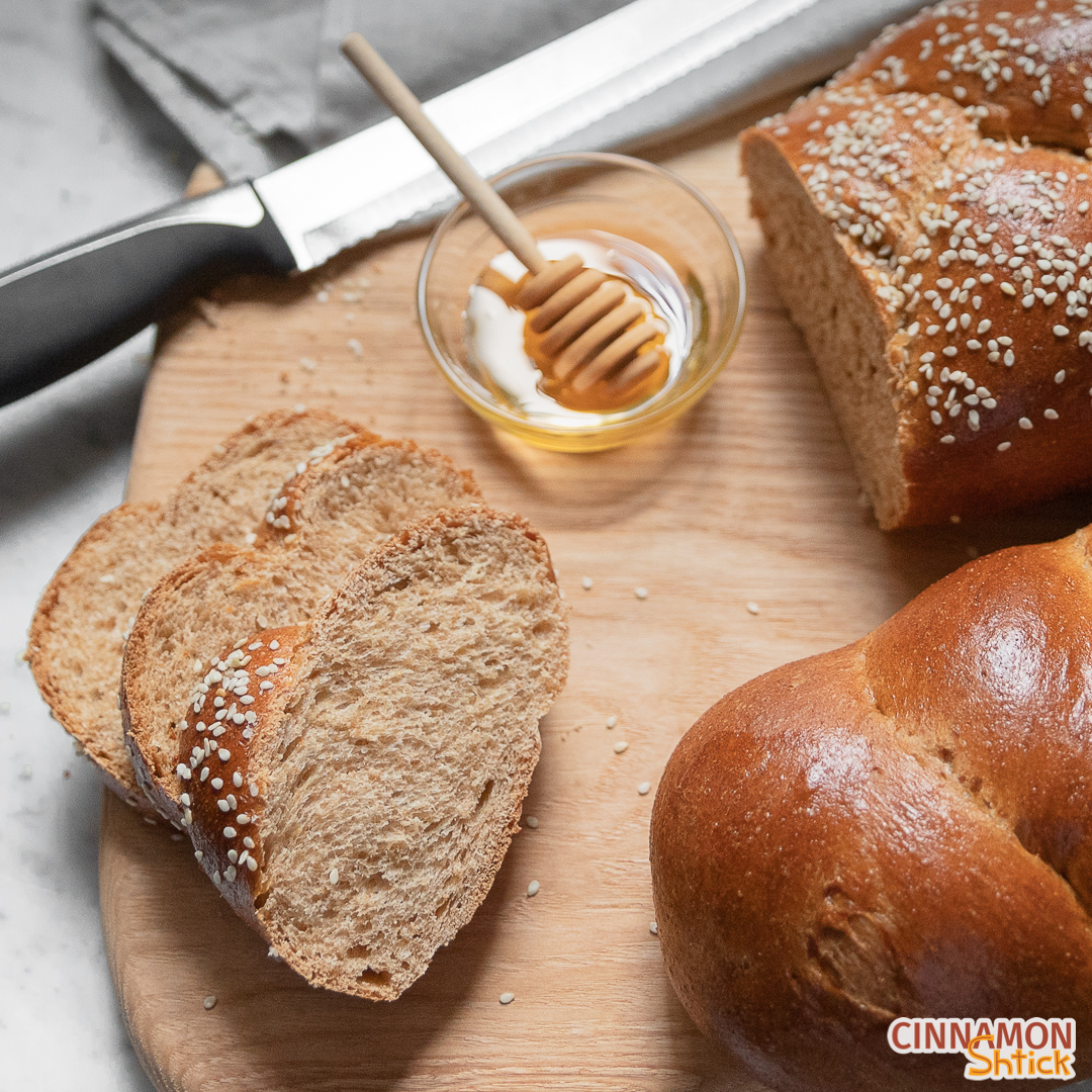 Three slices of whole wheat challah with a small bowl of honey