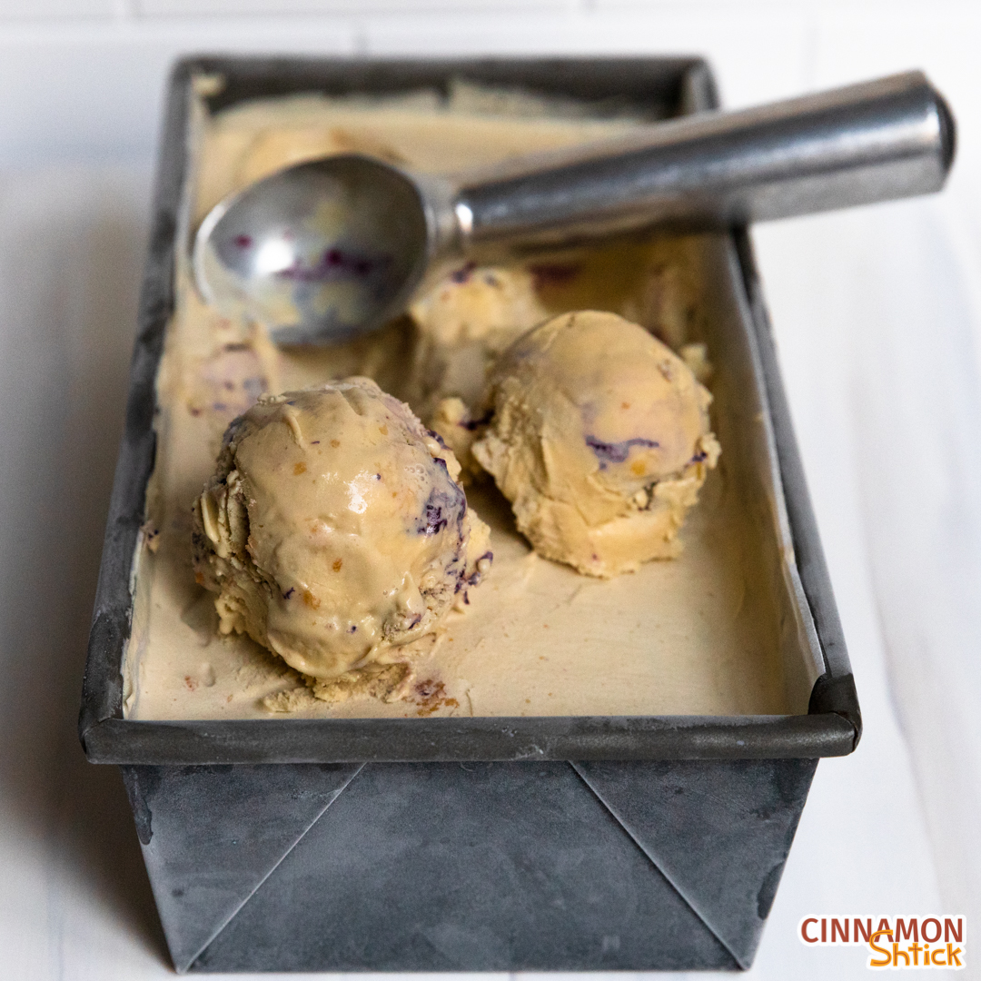 Container of Maple Blueberry Pie Ice Cream with two scoops in front and the ice cream scoop sitting in container behind the scoops.