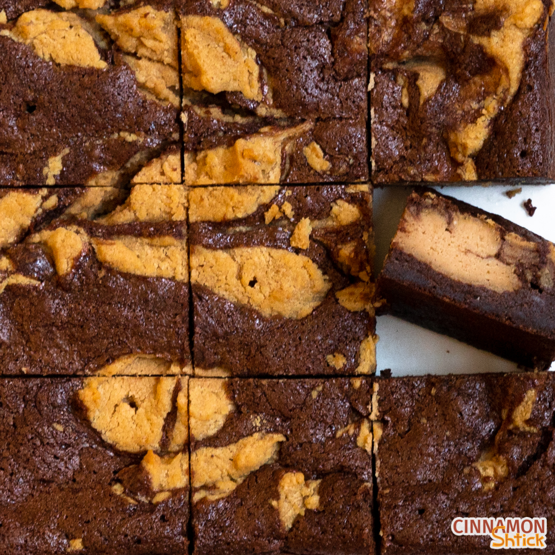 Square of Peanut Butter Cheesecake Brownies cut into 9 pieces with the brownie in the right column middle row, facing upward to see the inside of the brownie