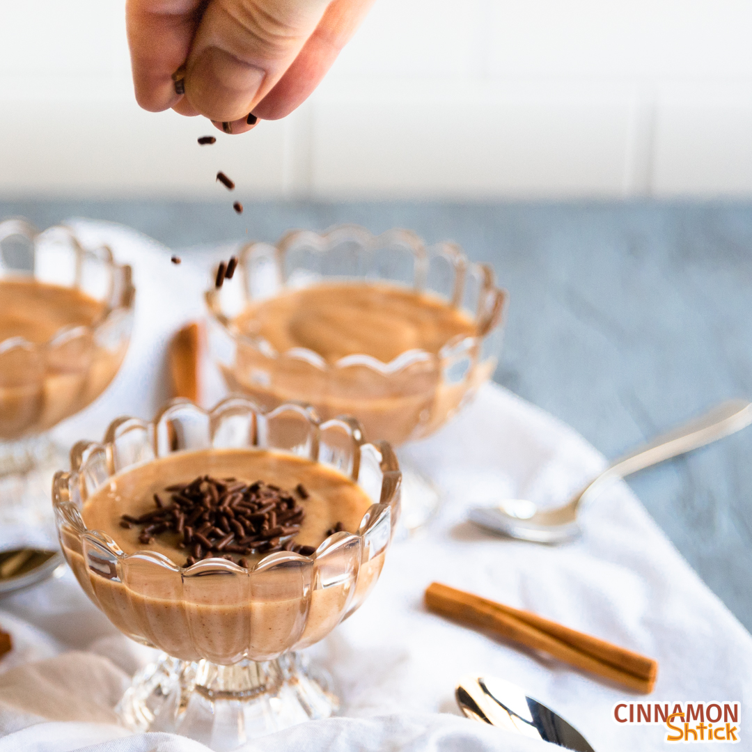 Several dishes of cinnamon pudding on table with spoons and cinnamon sticks with fingers dropping chocolate sprinkles on top of the dish in the forefront.