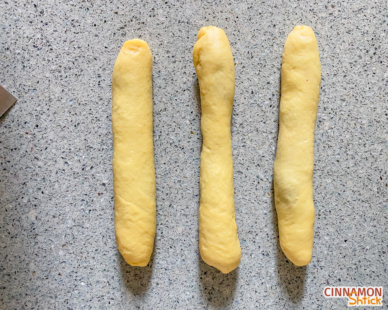 Three strands of dough, rolled up with the blueberry filling inside them.