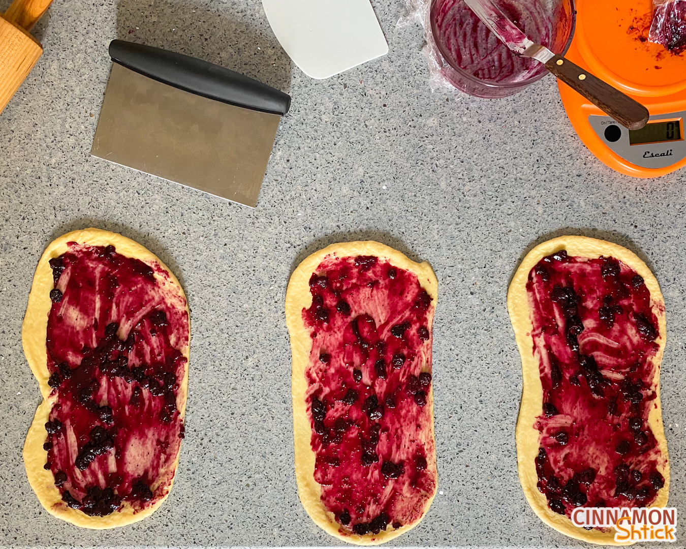 Three strands of challah dough rolled out to rectangles with blueberry filling spread on each.