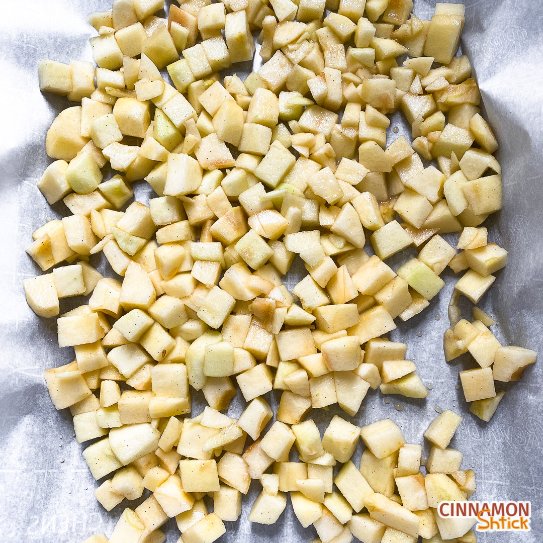 Chopped apples spread in a single layer on a baking sheet ready to be roasted
