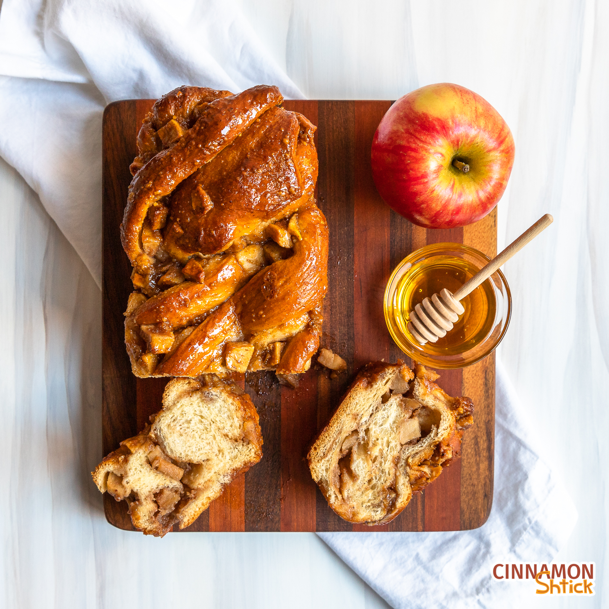 overhead view of apple honey babka on cutting board with a couple slices showing the inside, a bowl of honey and an apple