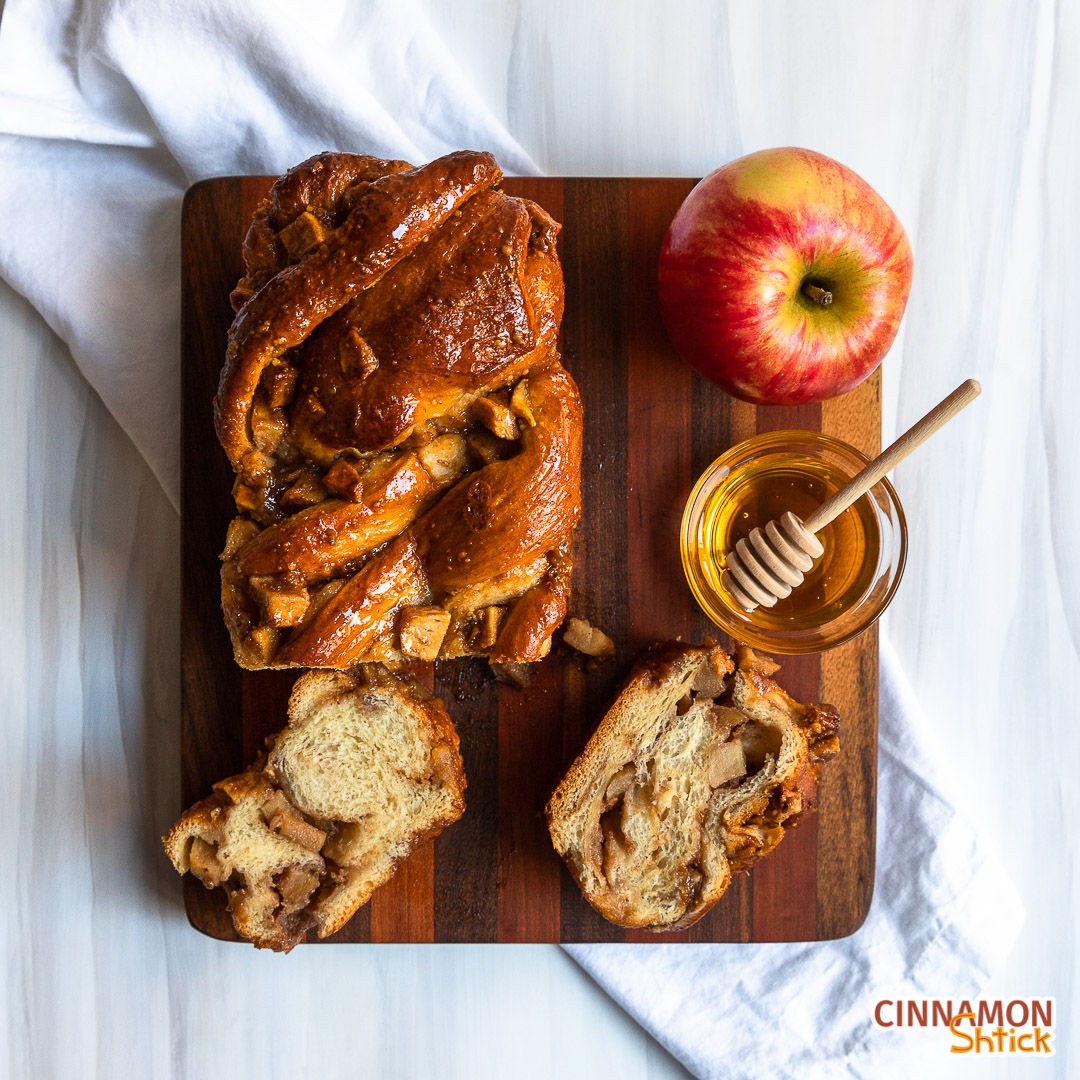 Top view of Apple Honey Babka and two slices with a bowl of honey and an apple.