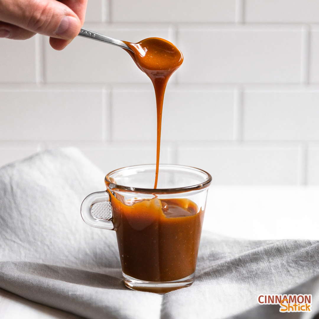 Caramel sauce dripping from a spoon.