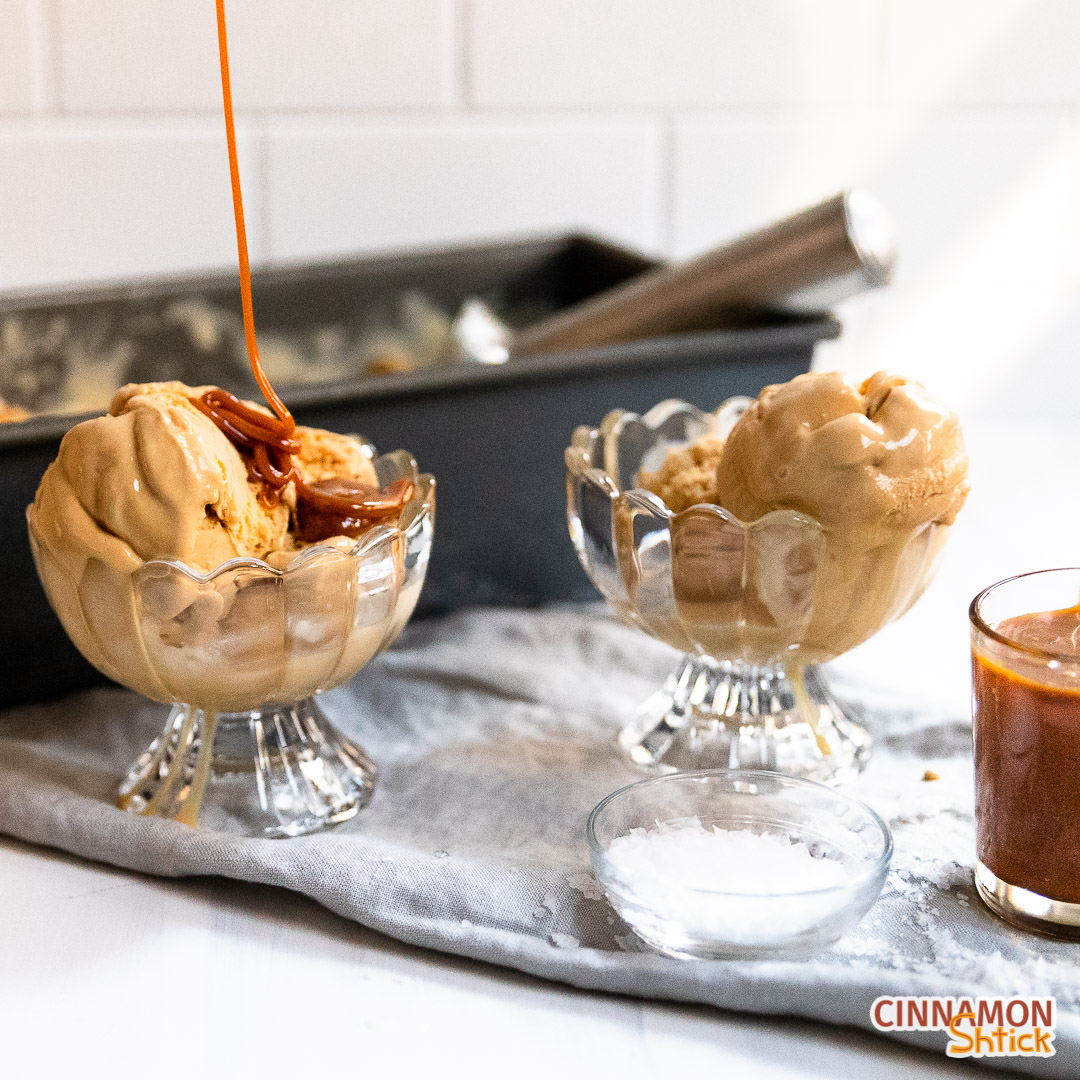 Two dishes of salted caramel ice cream with caramel sauce being poured on one of the dishes
