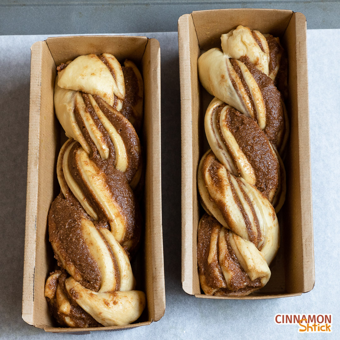 Two babkas in separate baking pans ready to be baked.