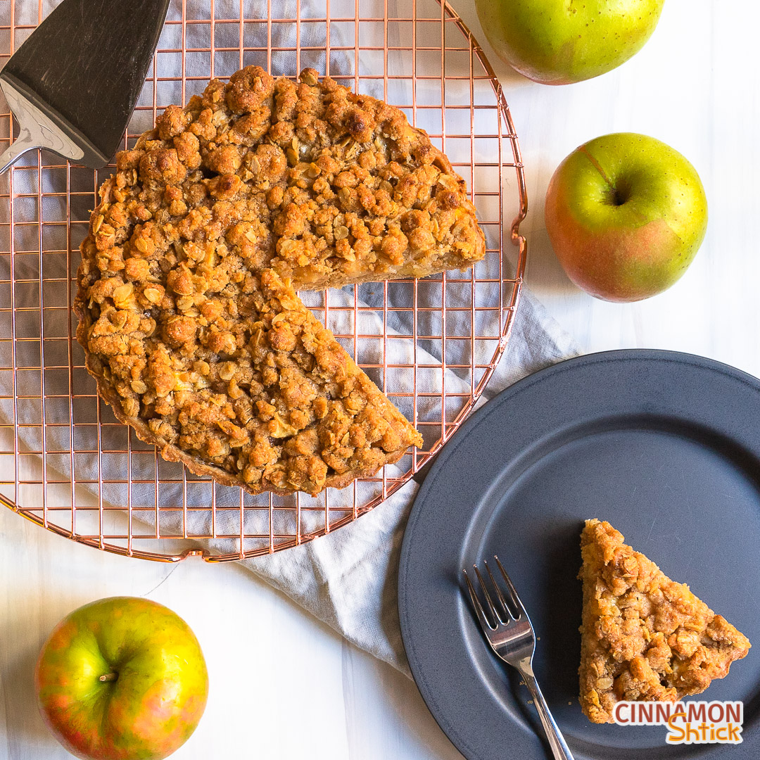 Slice of apple crumb tart on plate next to rest of tart on cooling rack