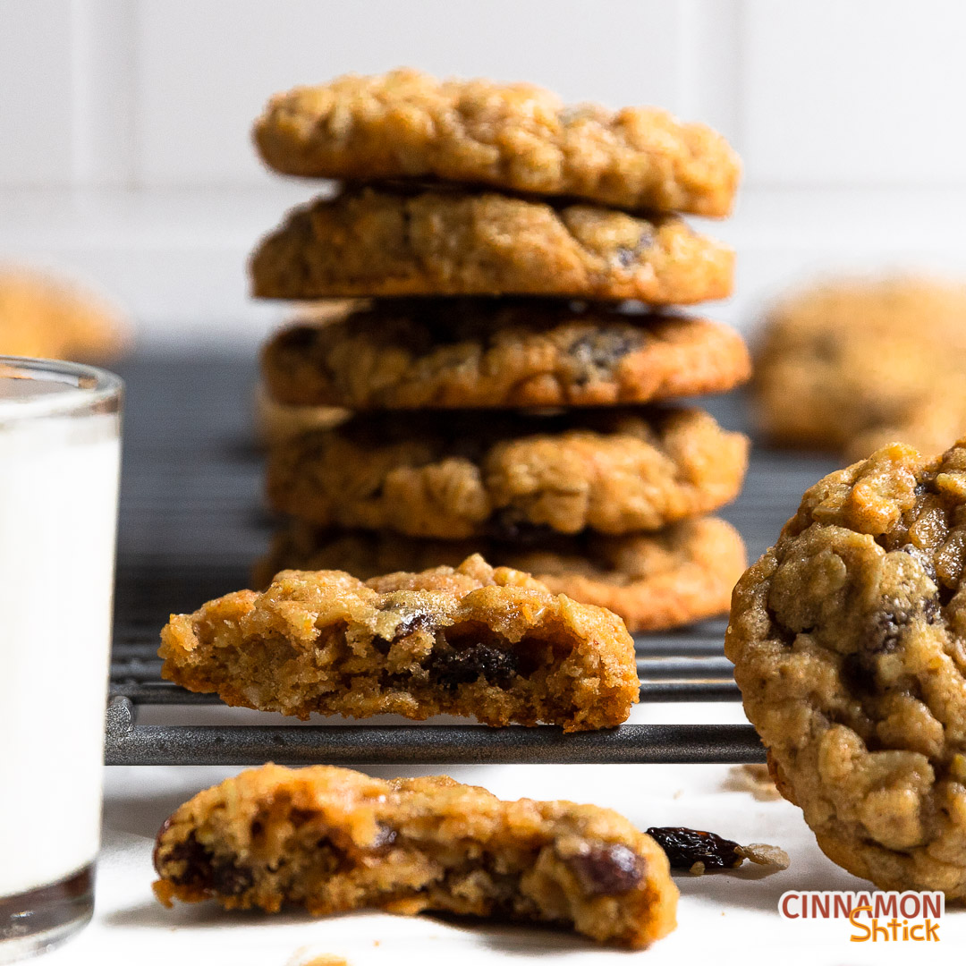 Stack of oatmeal raisin cookies with one broken in half in the front