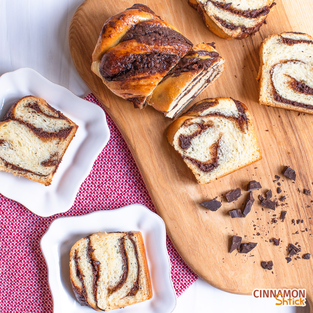 Two plated slices of brownie babka with slices on a cutting board