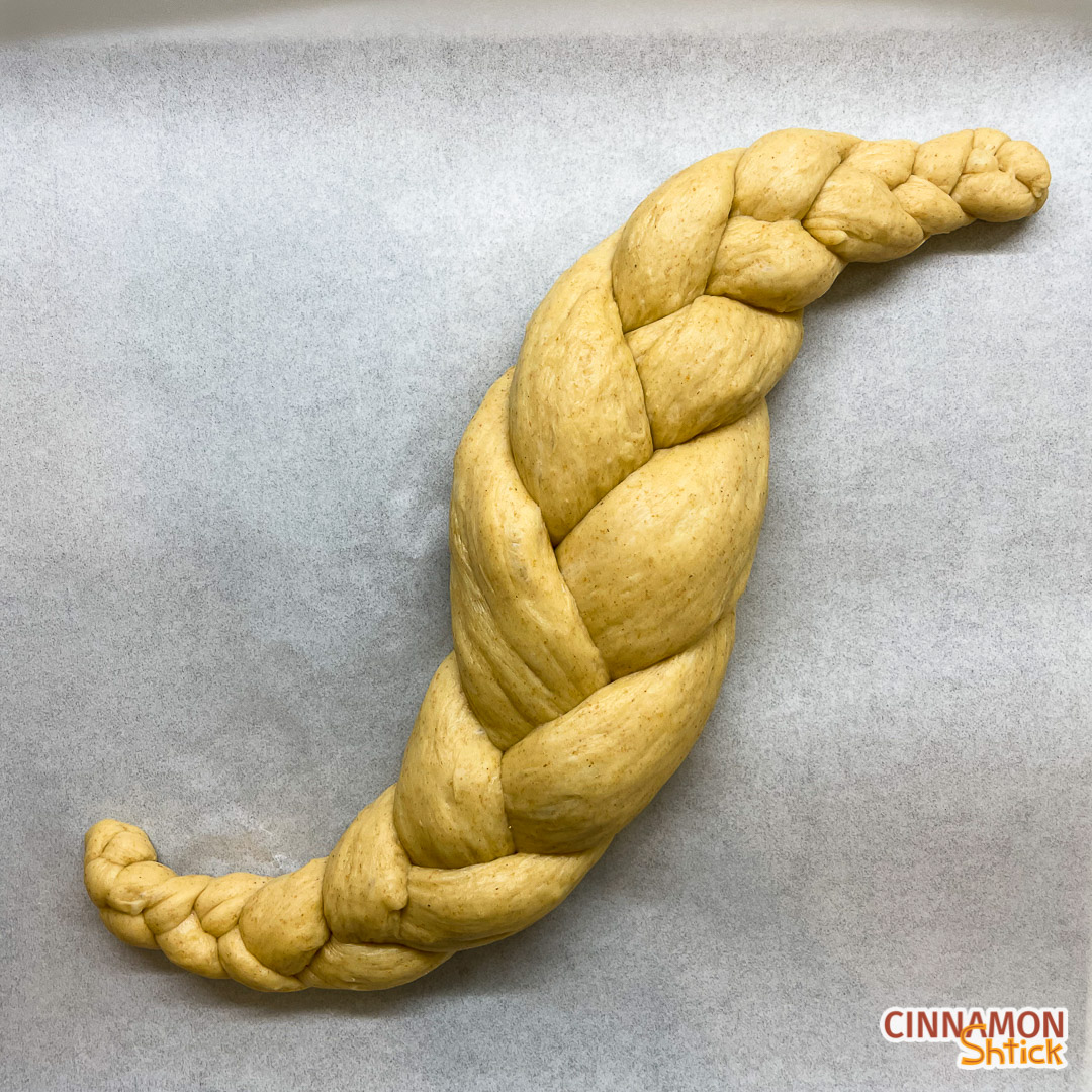 sourdough challah braided with 3 strands in the shape of an S