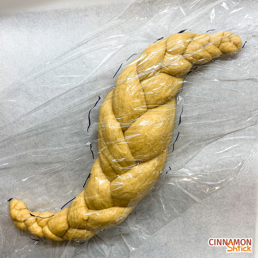 shaped sourdough challah with plastic wrap on it and markings to show its size