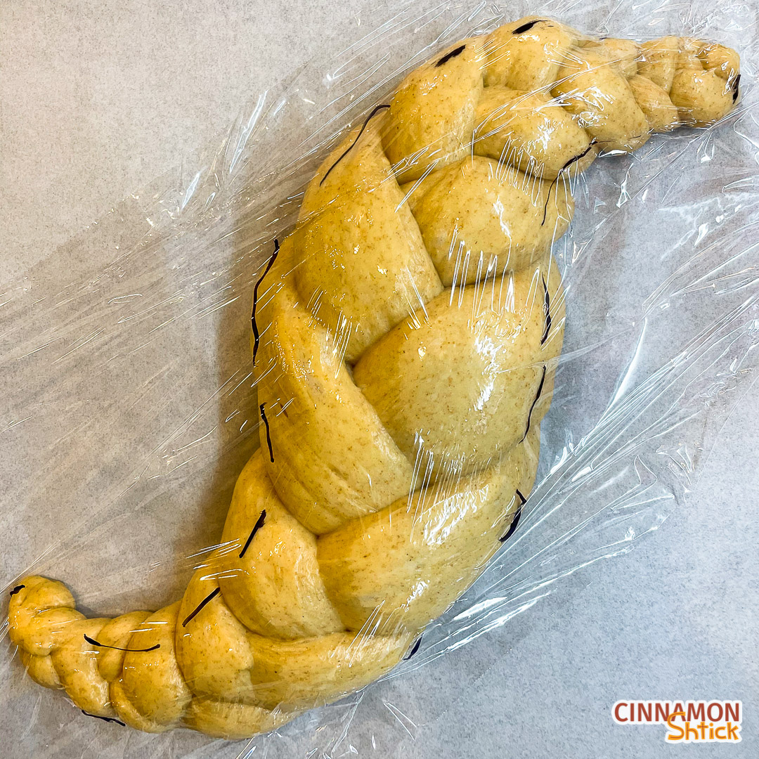 shaped sourdough challah with plastic wrap on it and markings to show how it has increased in size