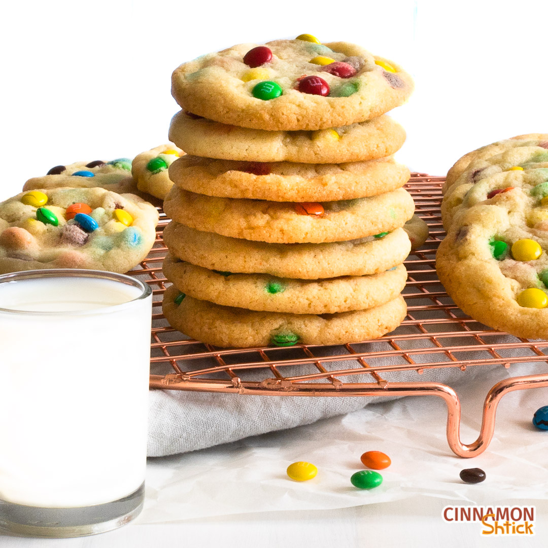 Stack of M&M cookies on cooling rack with glass of milk in forefront