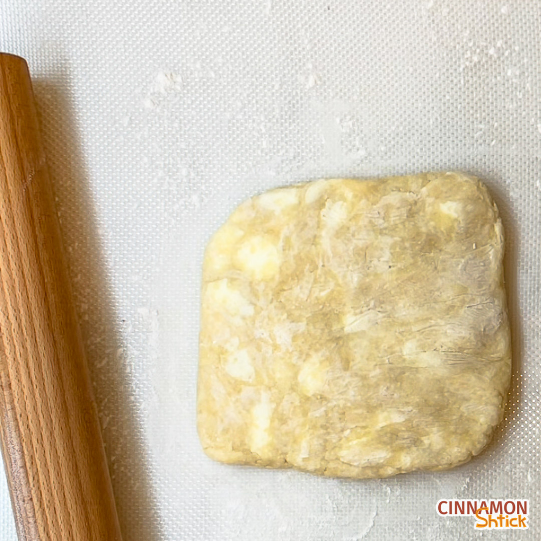 dough with rolling pin on lightly floured surface