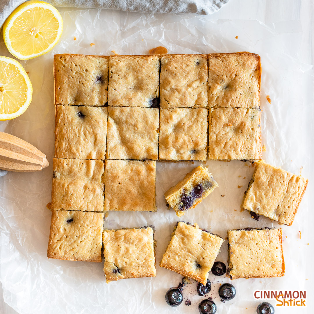 lemon blueberry blondies cut into square with a few misplaced in the front and one on its side