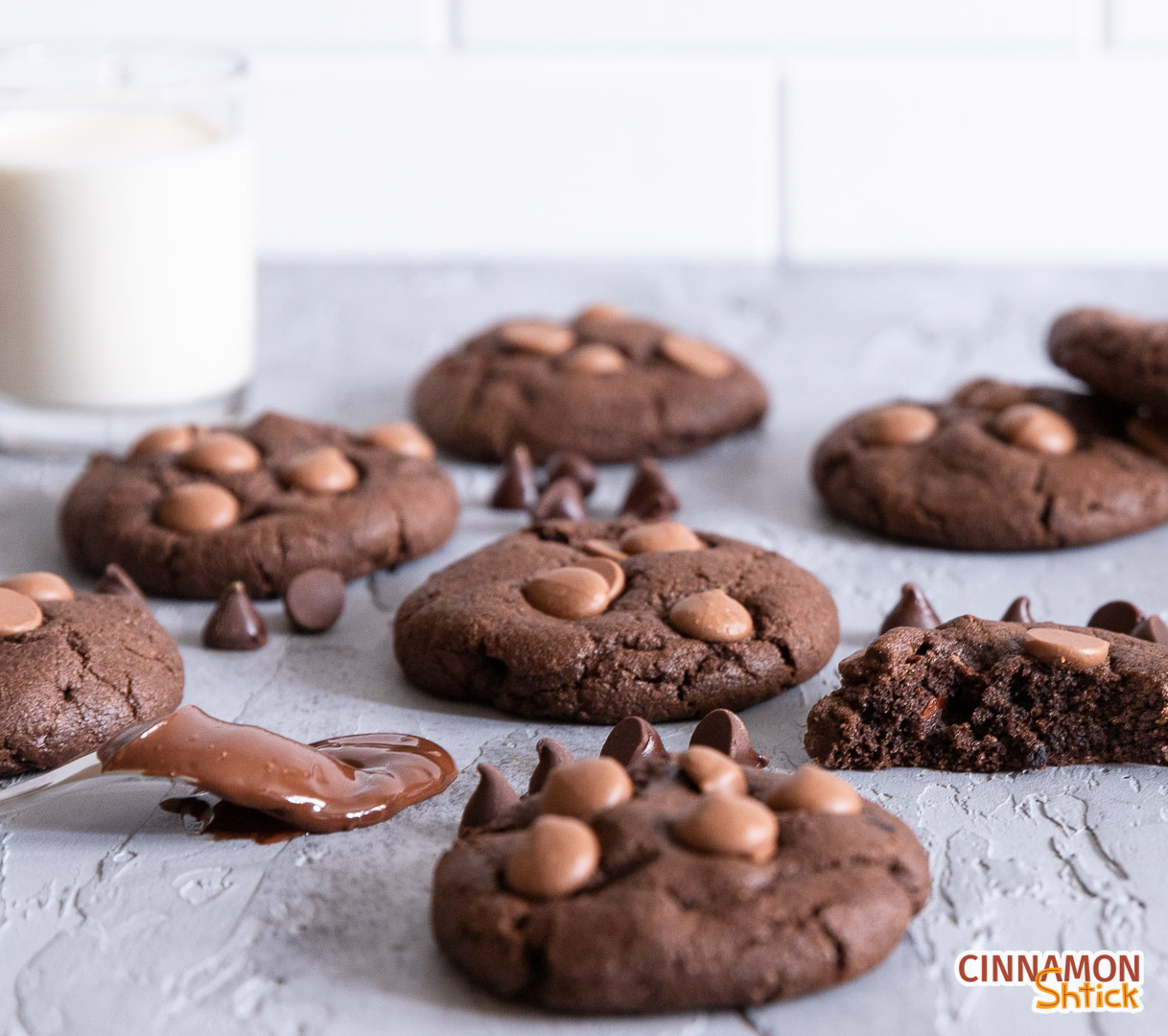 chocolate chocolate chip cookies on counter with glass of milk in background
