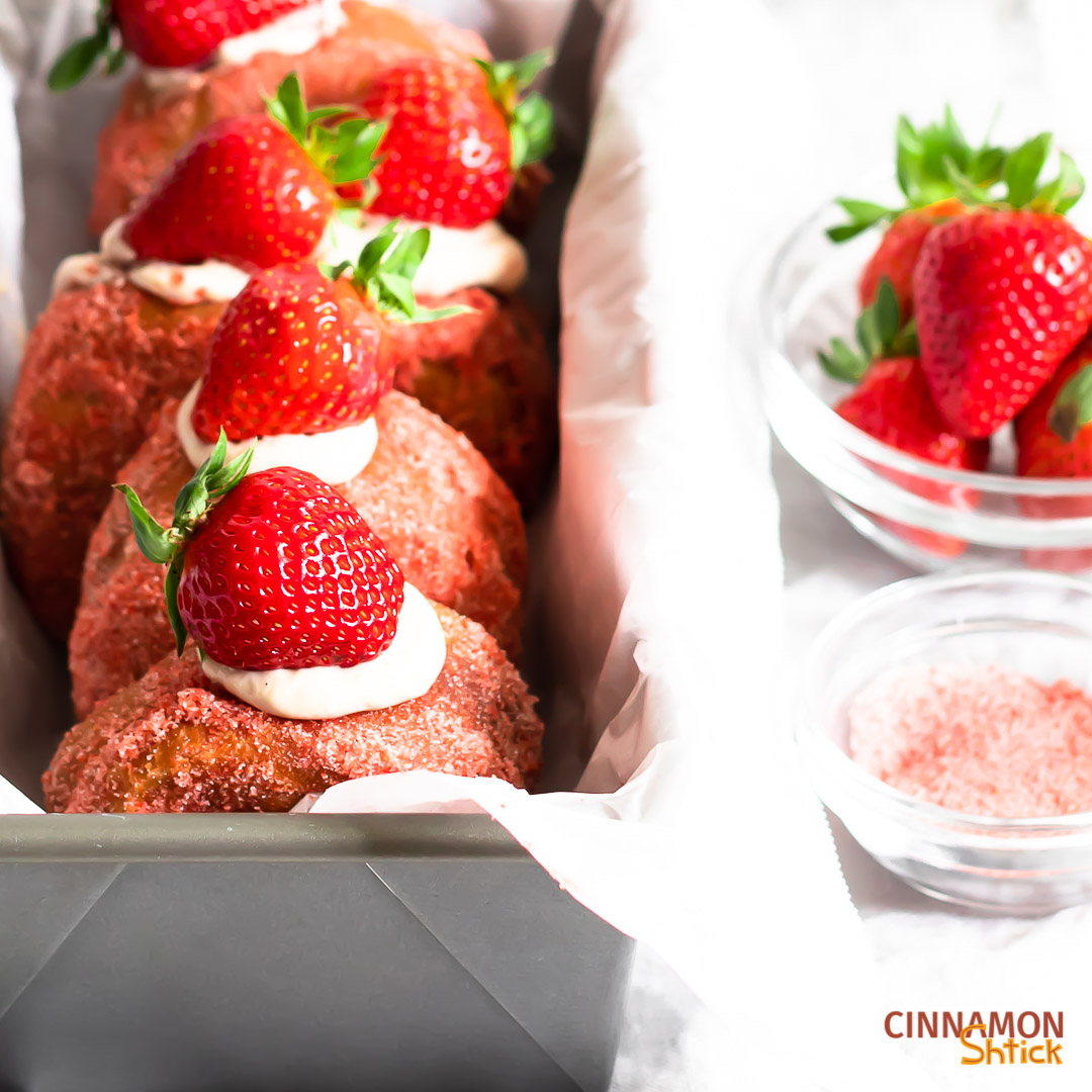 Strawberry donuts in a loaf pan on the left side of frame, with a bowl of strawberries and a bowl of strawberry sugar in the right frame.