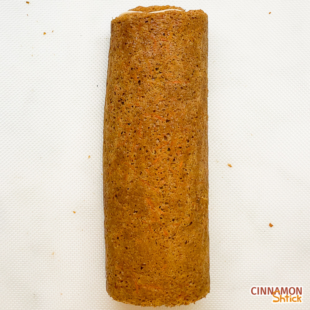 top view of frosted and rolled up graham carrot cake roll