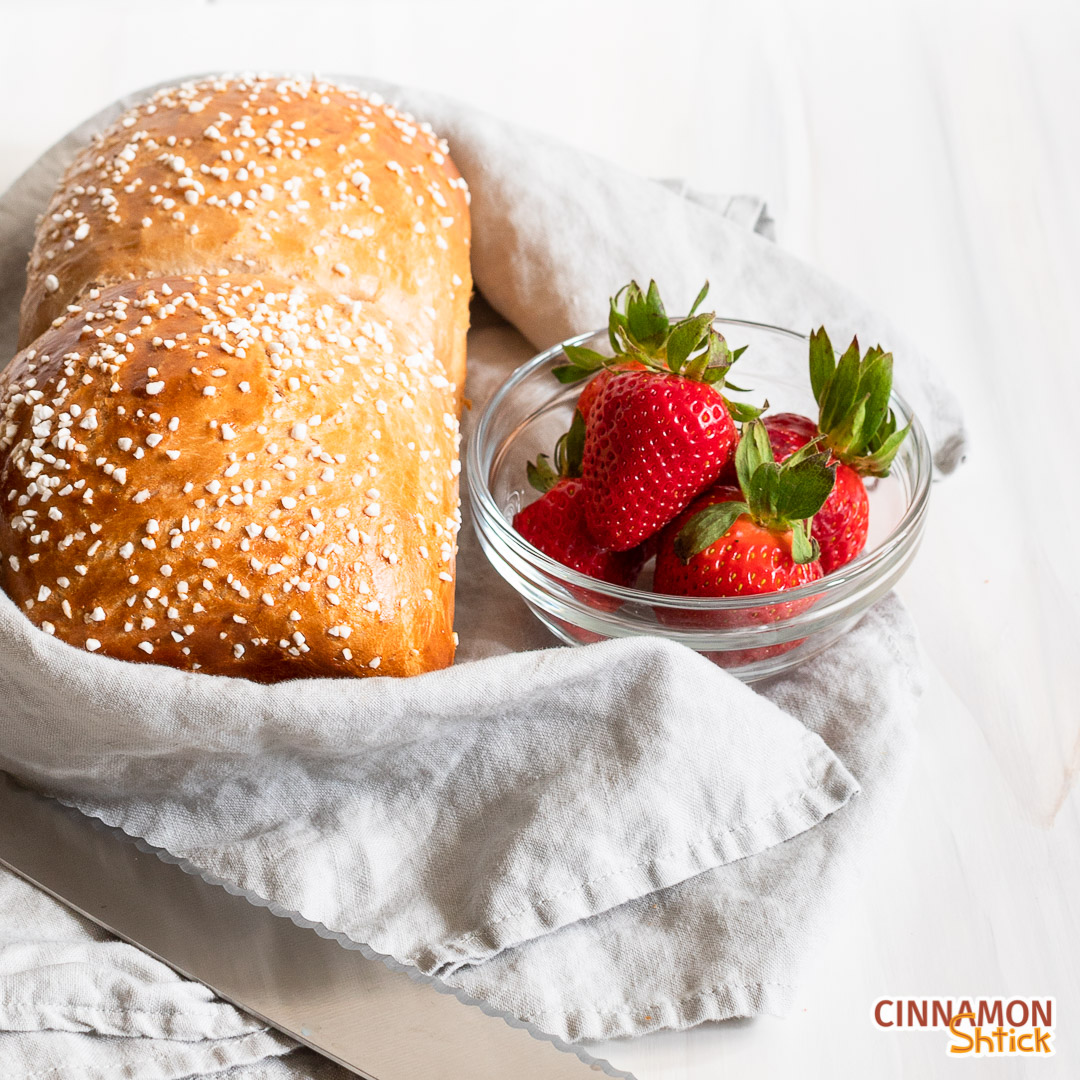 one loaf of strawberry brioche with a gray napkin wrapped around it and a bowl of strawberries to the righ