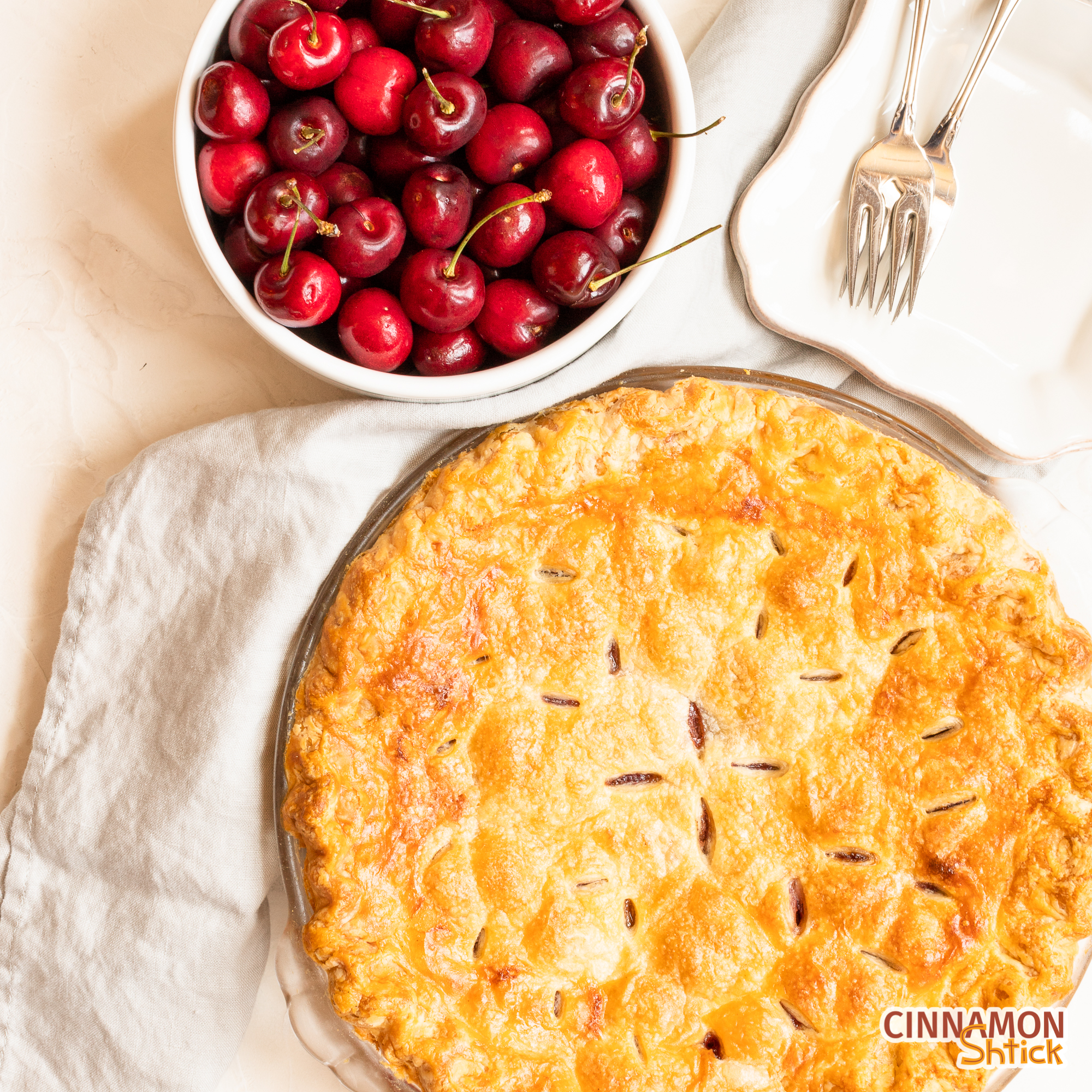 overhead view of cherry pie with bowl of cherries in upper portion