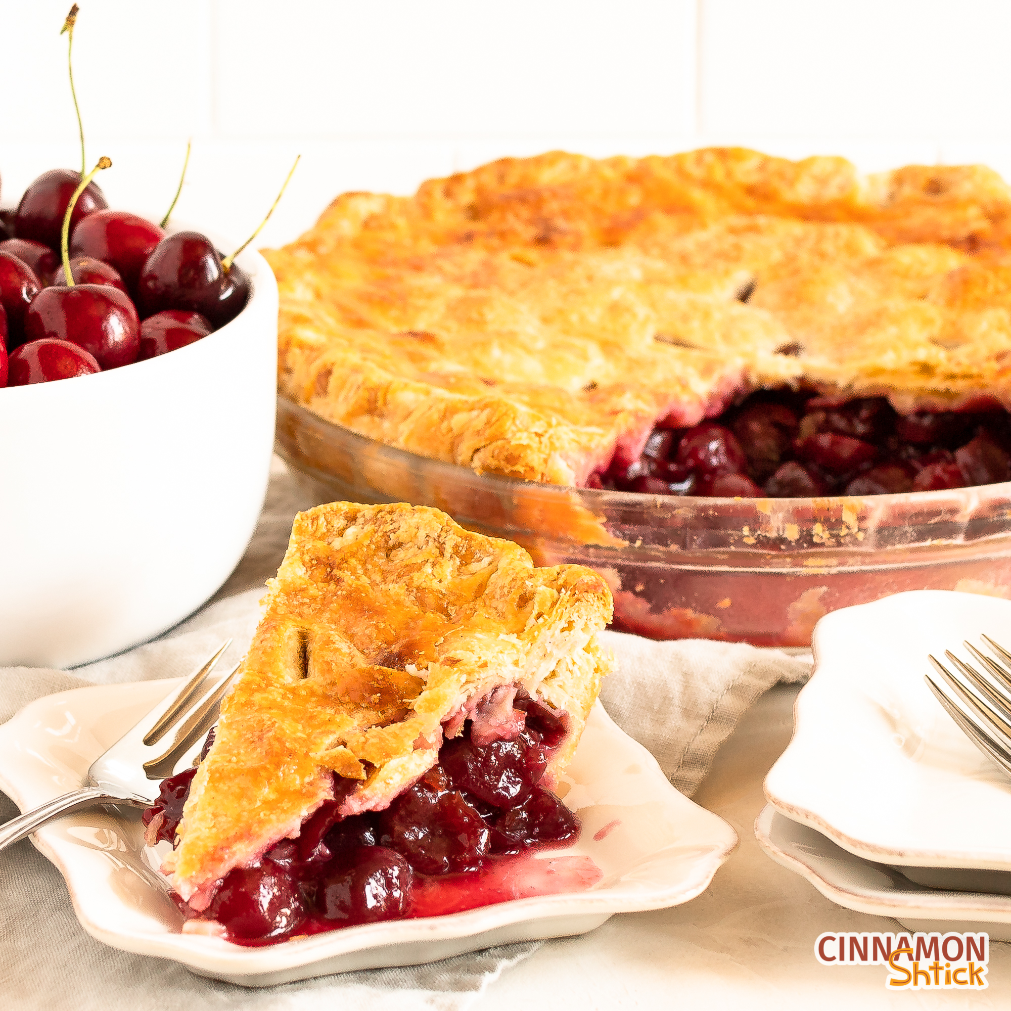 slice of cherry pie on a plate with rest of pie and bowl of cherries in background