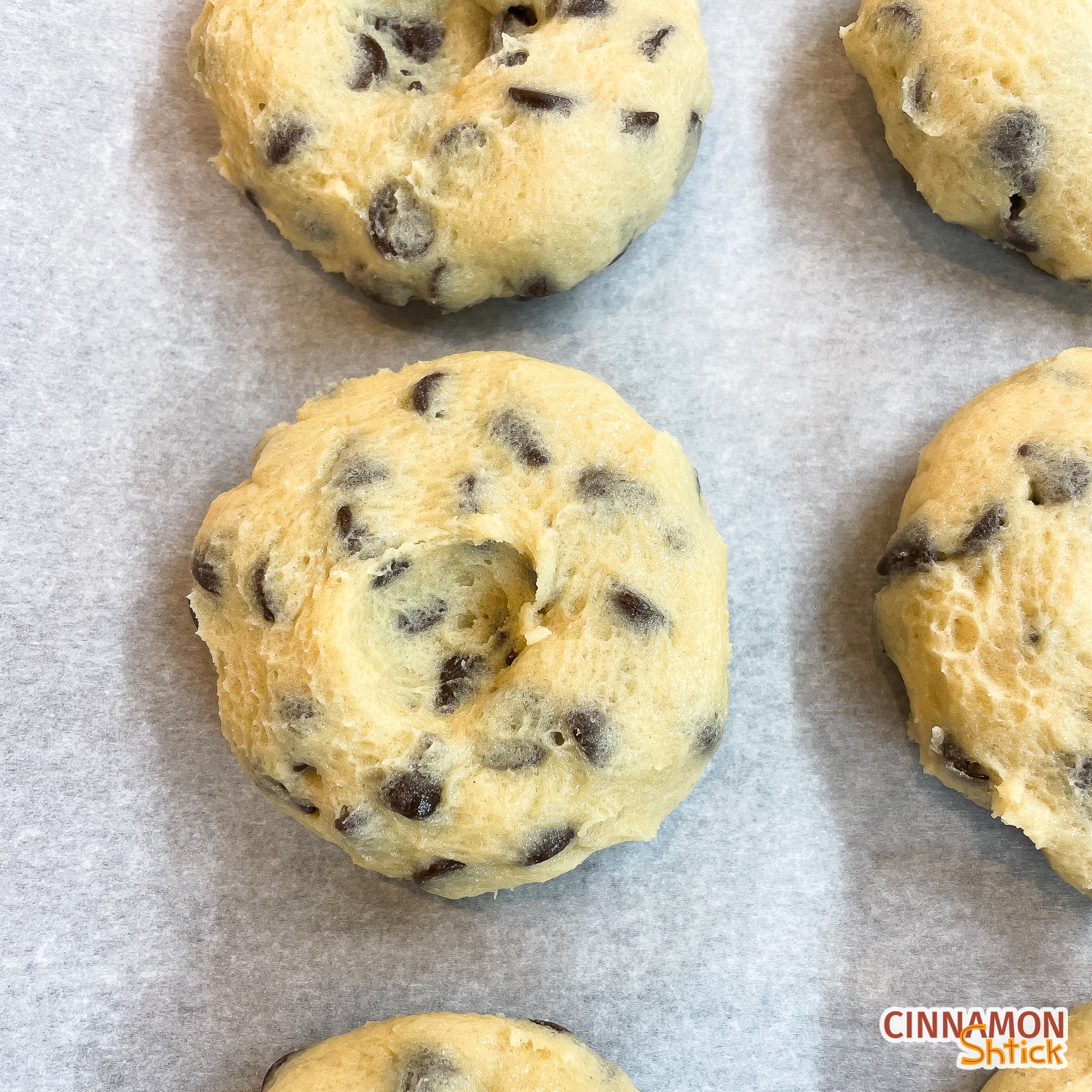 Cookie dough pucks lined up on parchment covered baking sheet