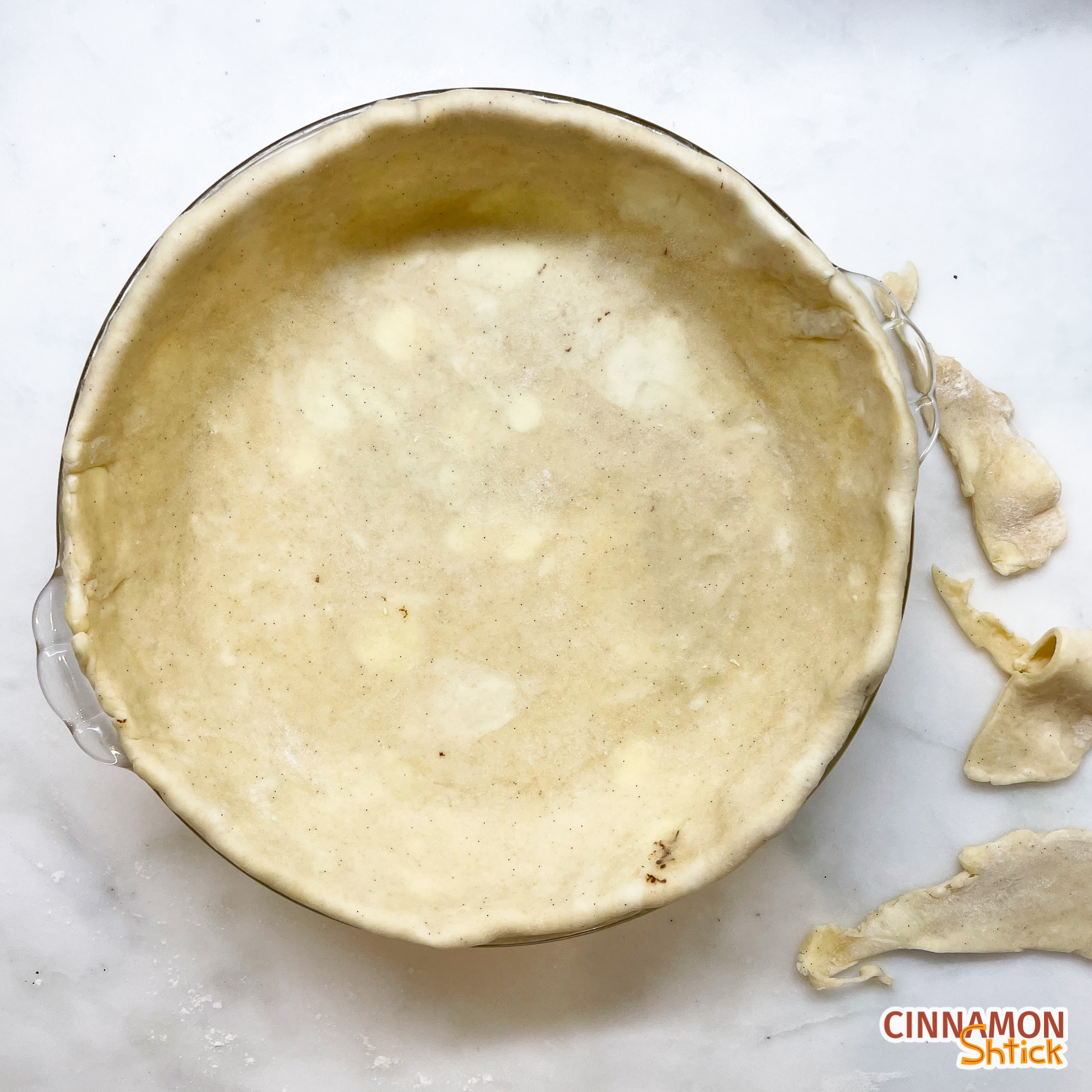side view of pie dough in pie plate showing that the overhand was tucked into the pie dish with some scraps on the side