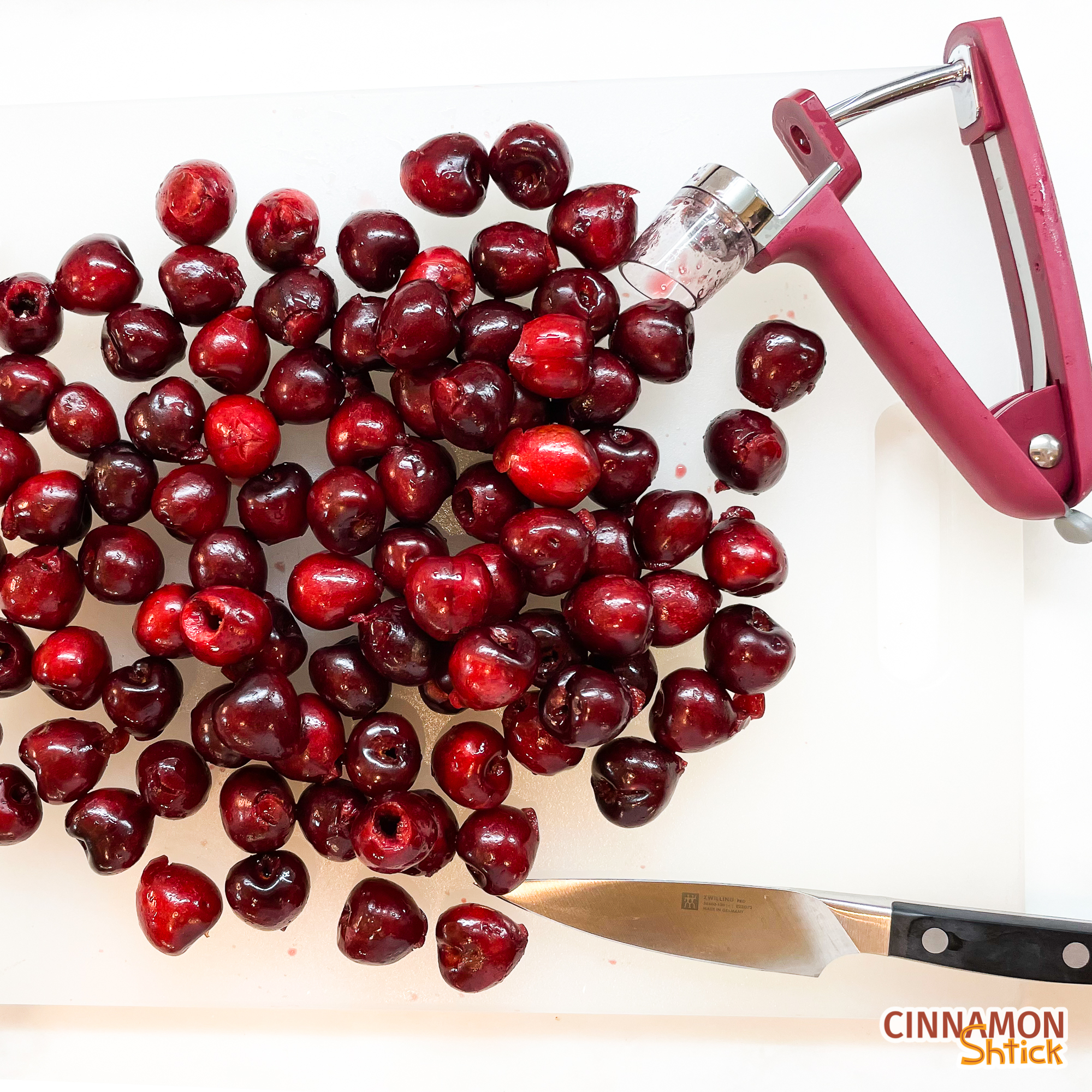 Pitted cherries on cutting board with cherry pitter and a paring knife