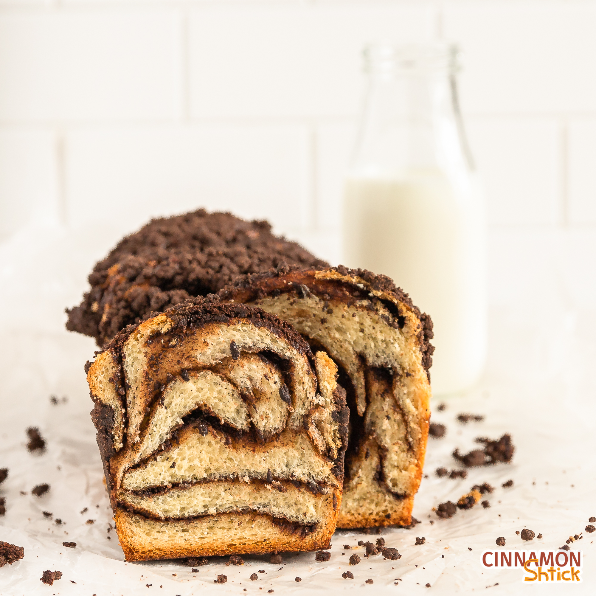 straight on shot of chocolate crumb babka showing the chocolate swirls in the babka with a bottle of milk in background