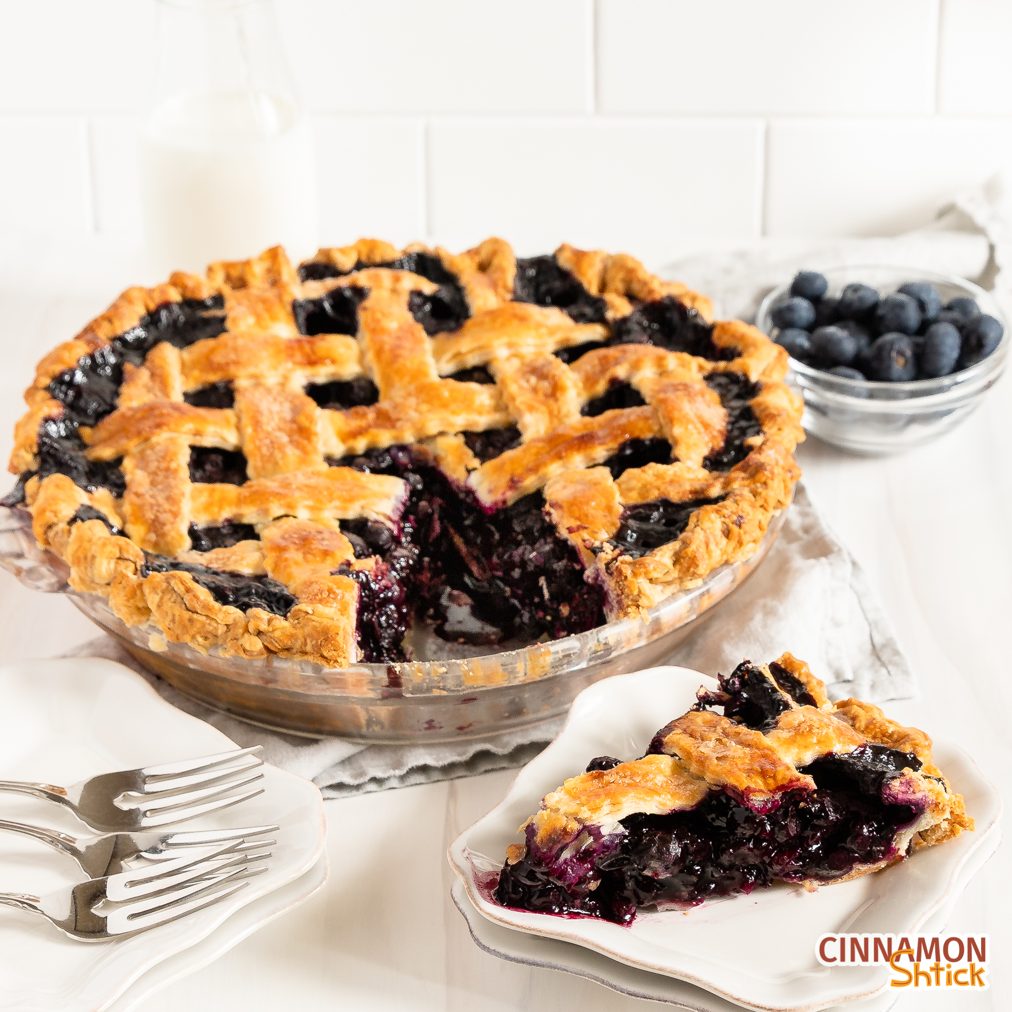 slice of blueberry pie on a plate with rest of pie behind it