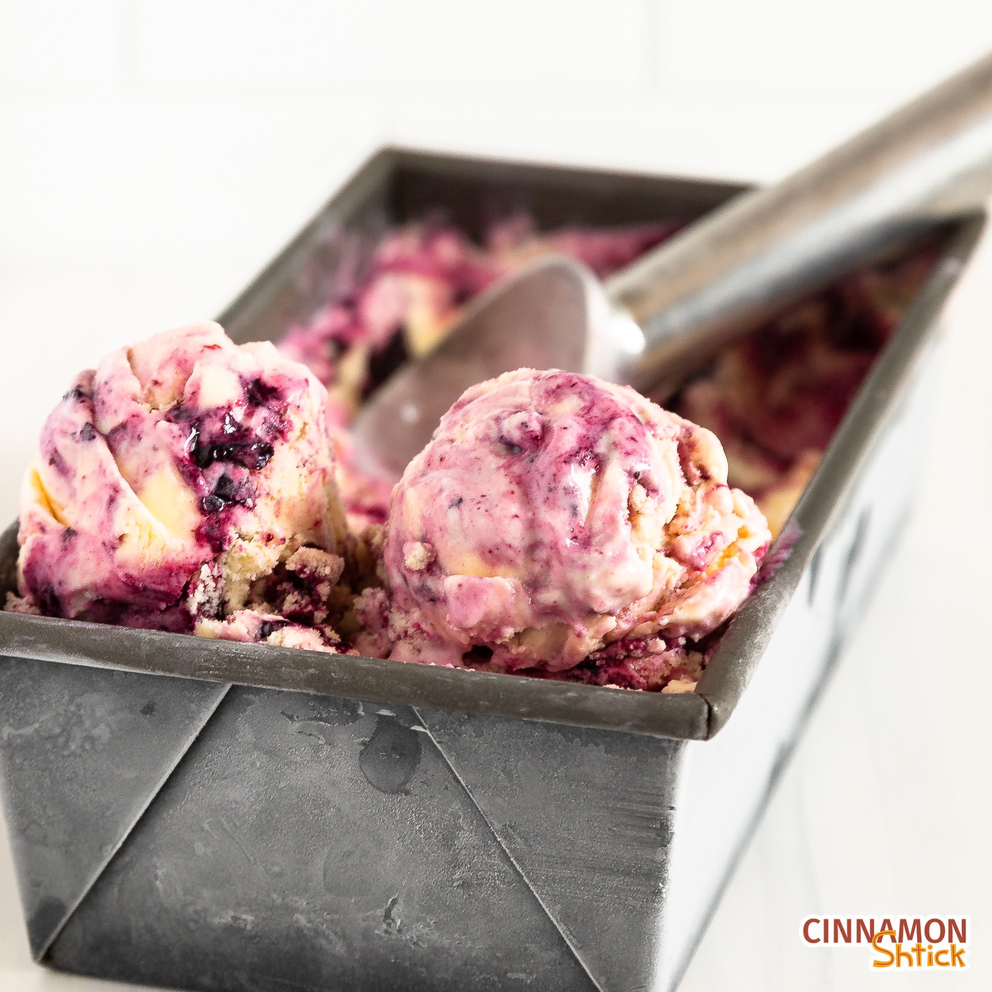 loaf pan with lemon blueberry ice cream, showing two scoops in front with ice cream scooper in background
