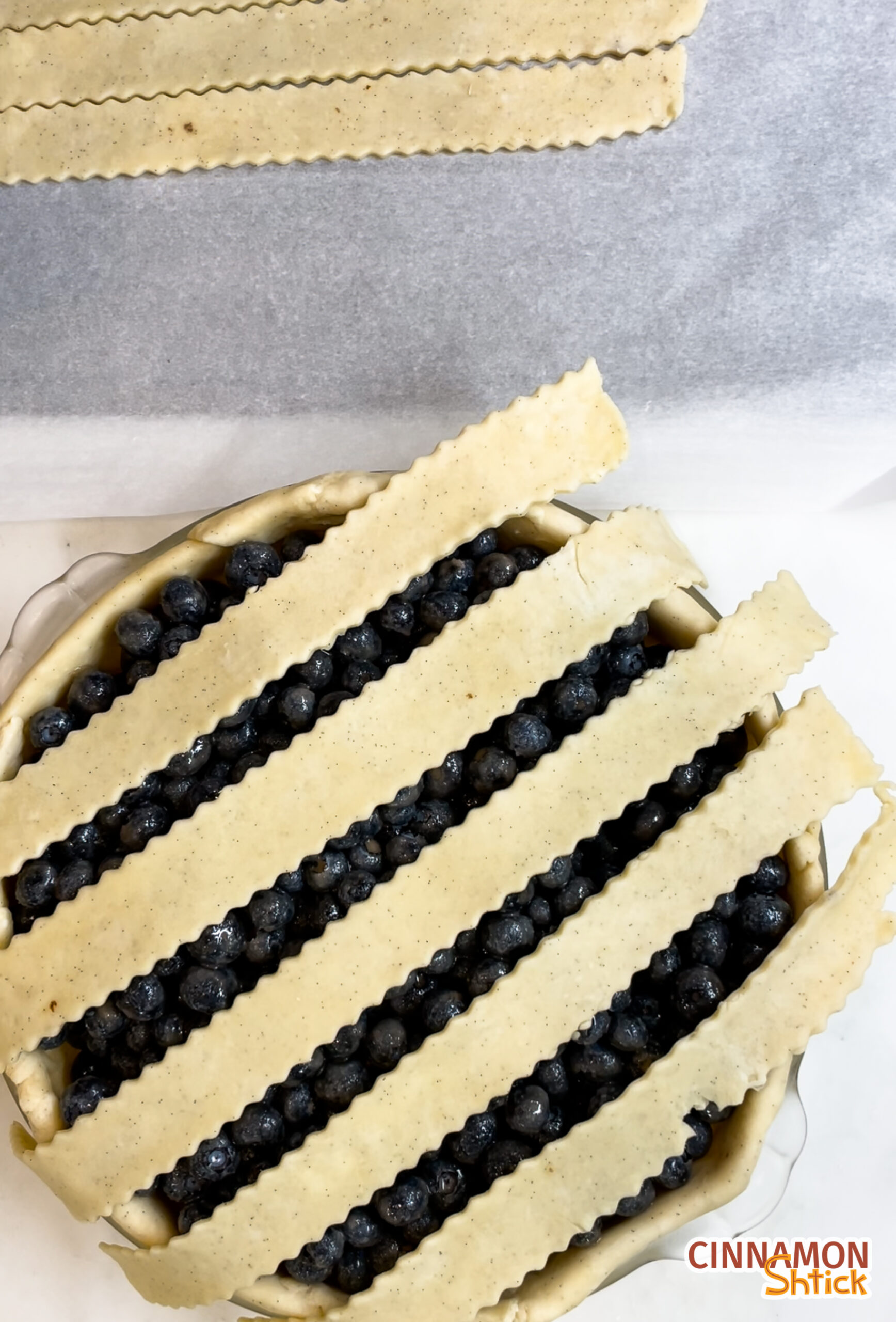 overhead view of pie dough strips over a blueberry pie