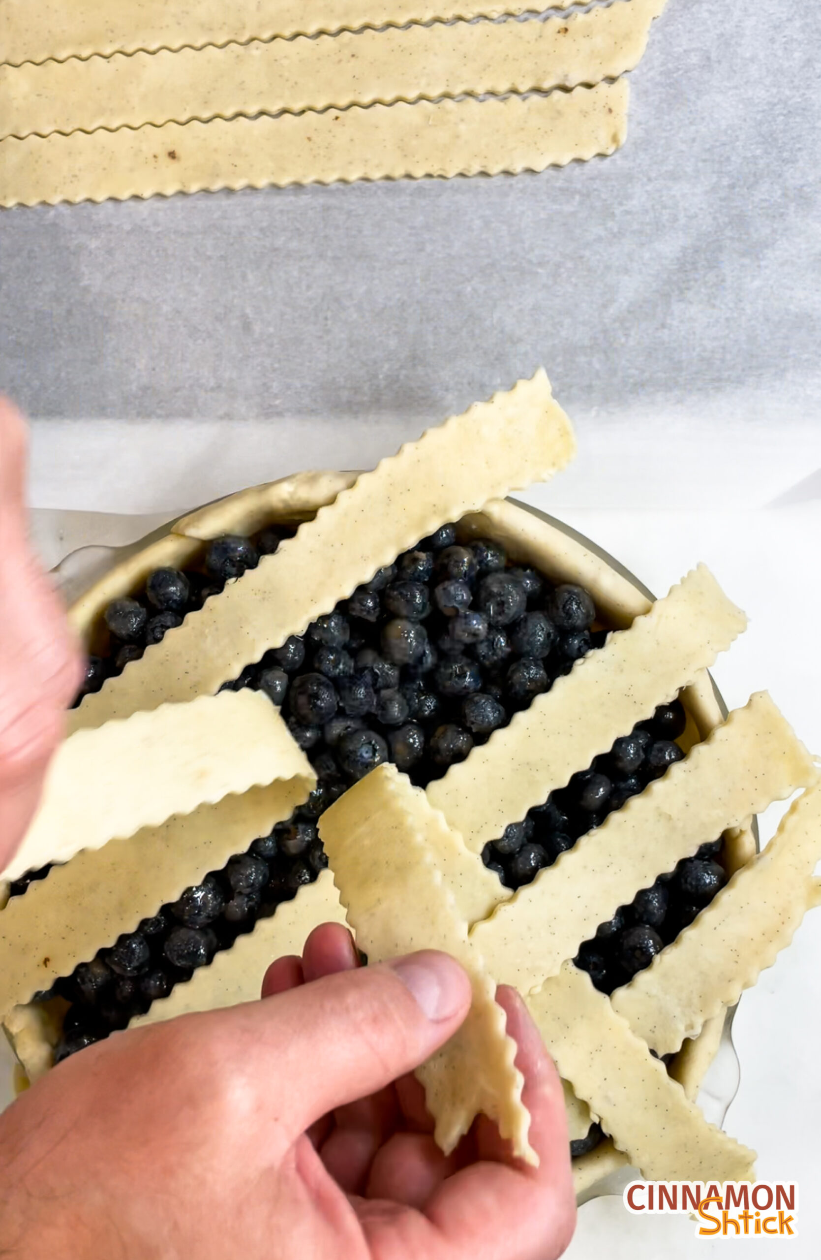 overhead view of the middle of placing cross-strips of pie dough to form a lattice