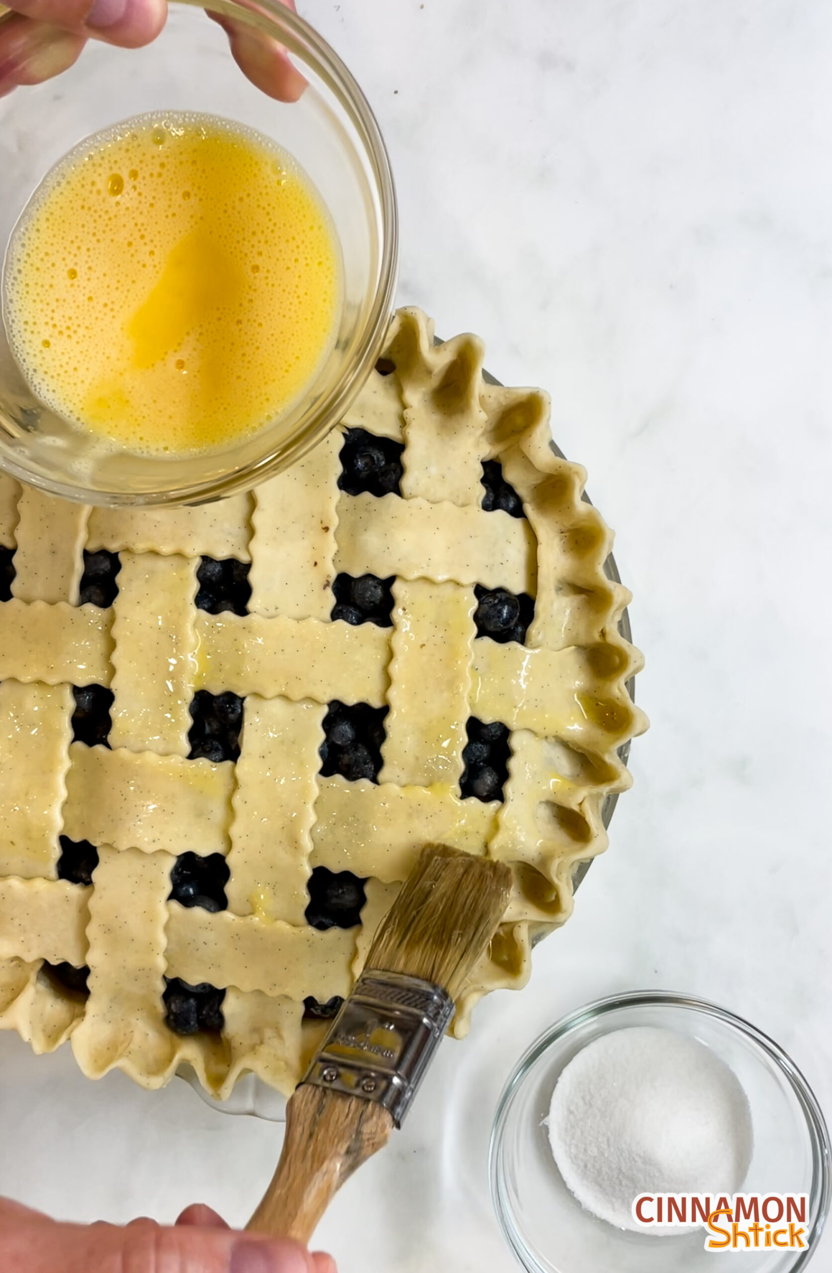 overhead view of lattice top pie crust being egg washed with bowl of sugar on counter