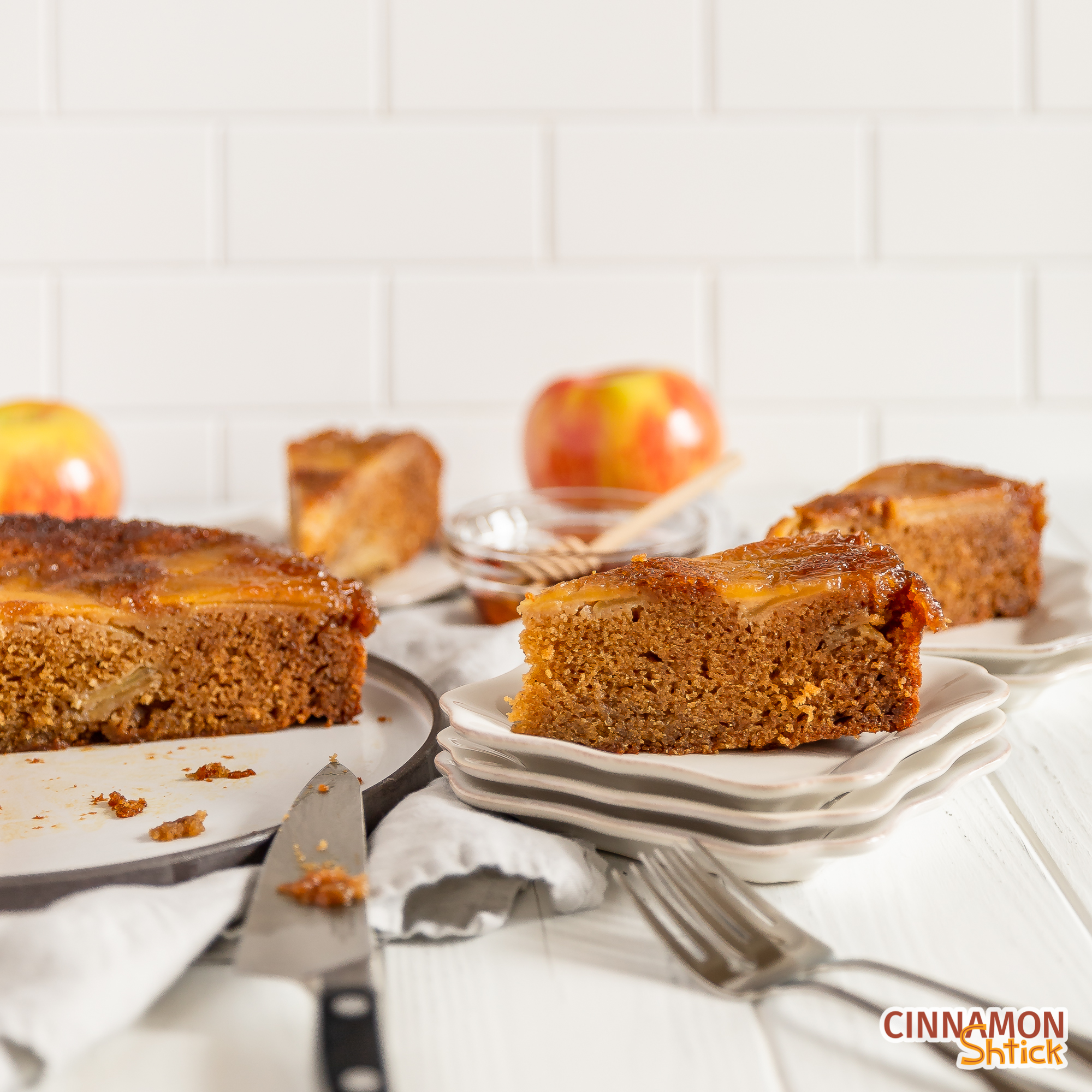 slice of honey upside down apple cake with two other slices in background and rest of cake with an apple