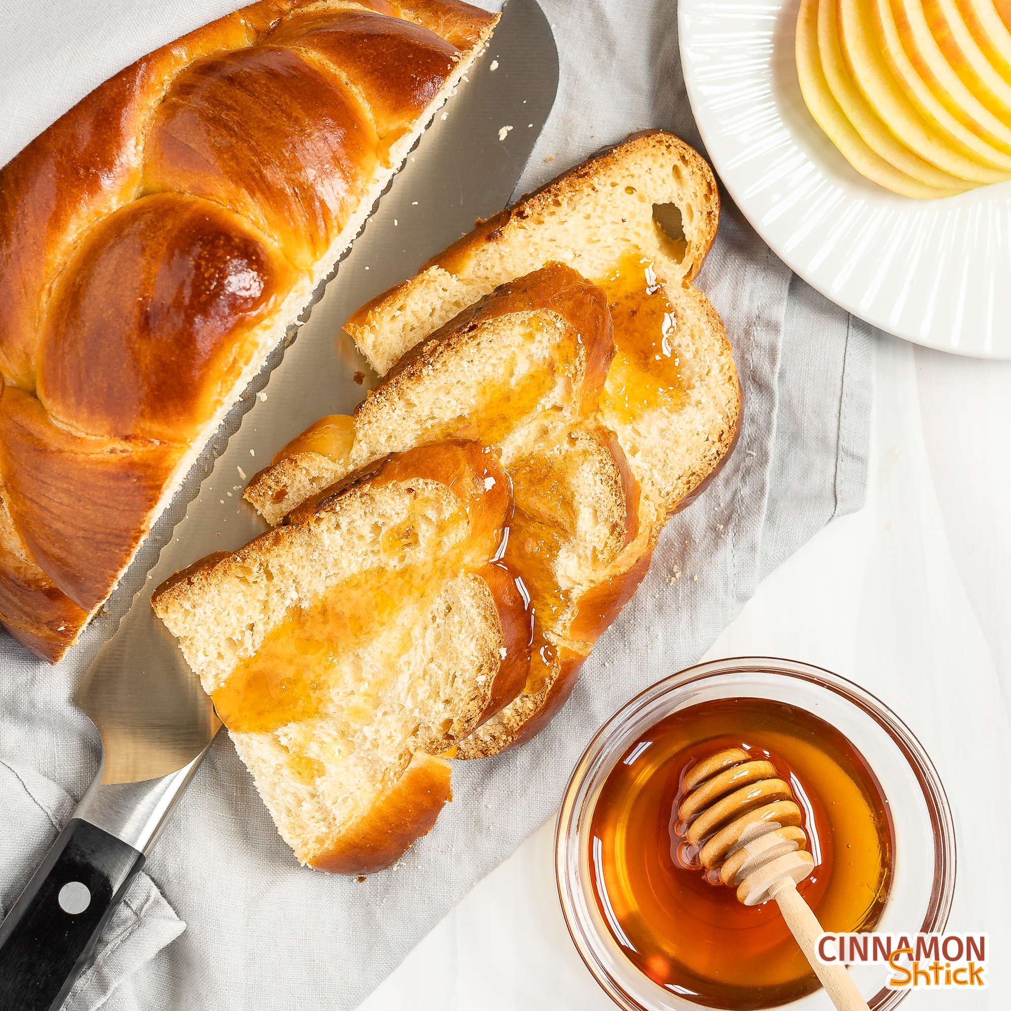 overhead view of half of a 4 strand round challah sliced with honey dripped on several pieces. Shown with a bowl of honey and a dish of sliced apples