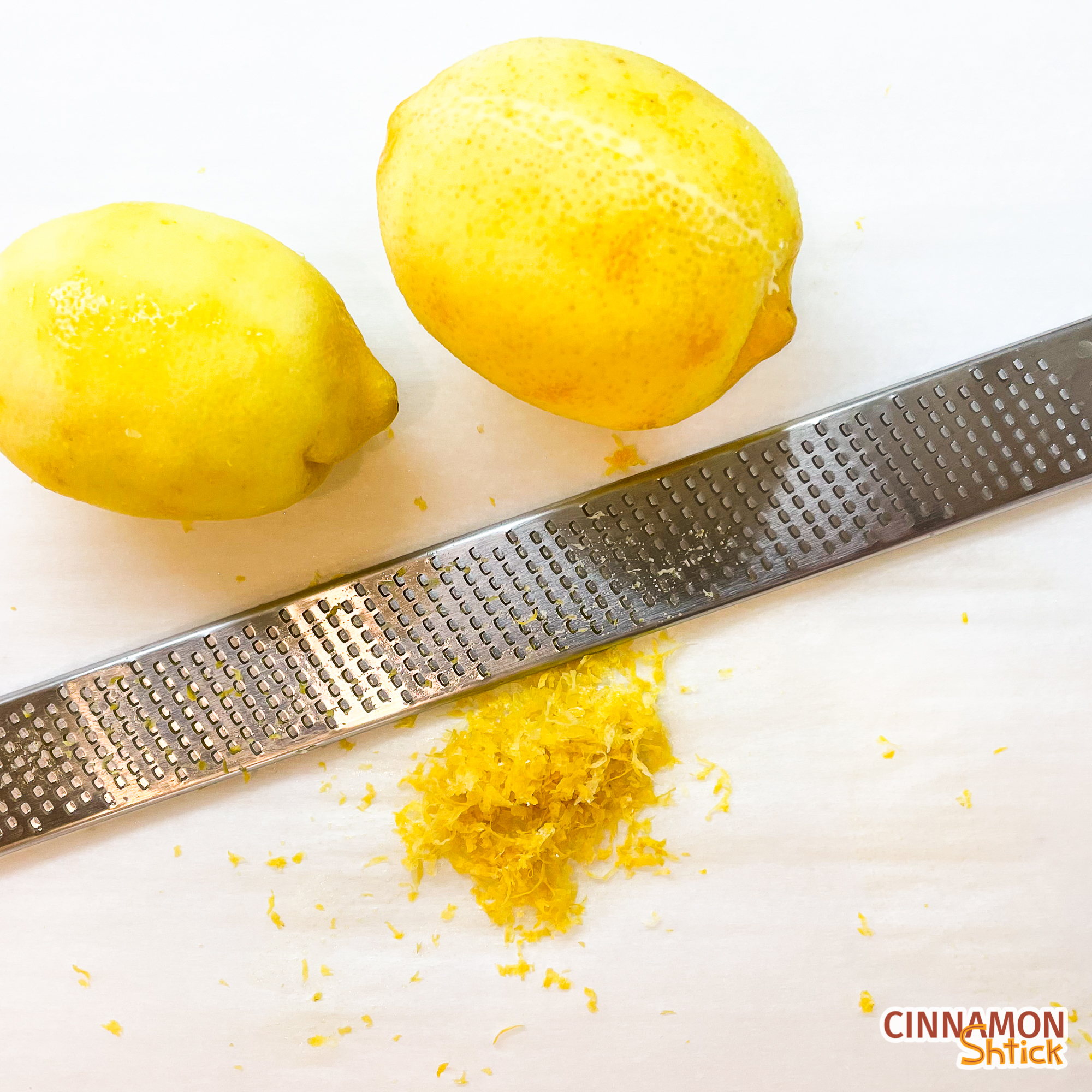 two lemons, zested, shown with zester and mound of lemon zest