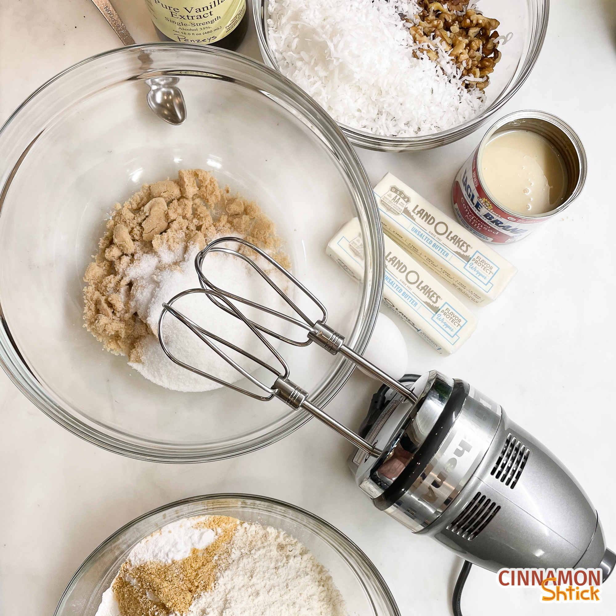 overhead view of hand mixer with bowl of sugars, bowl of dry ingredients, bowl of mix-ins, vanilla, butter, condensed milk
