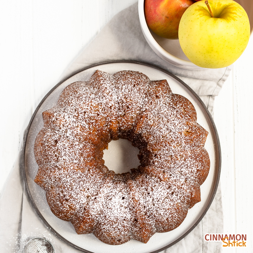 overhead view of apple bundt cake with confectioner's sugar sprinkled on top with a bowl of apples in the upper right corner and a handheld sifter in the bottom left corner