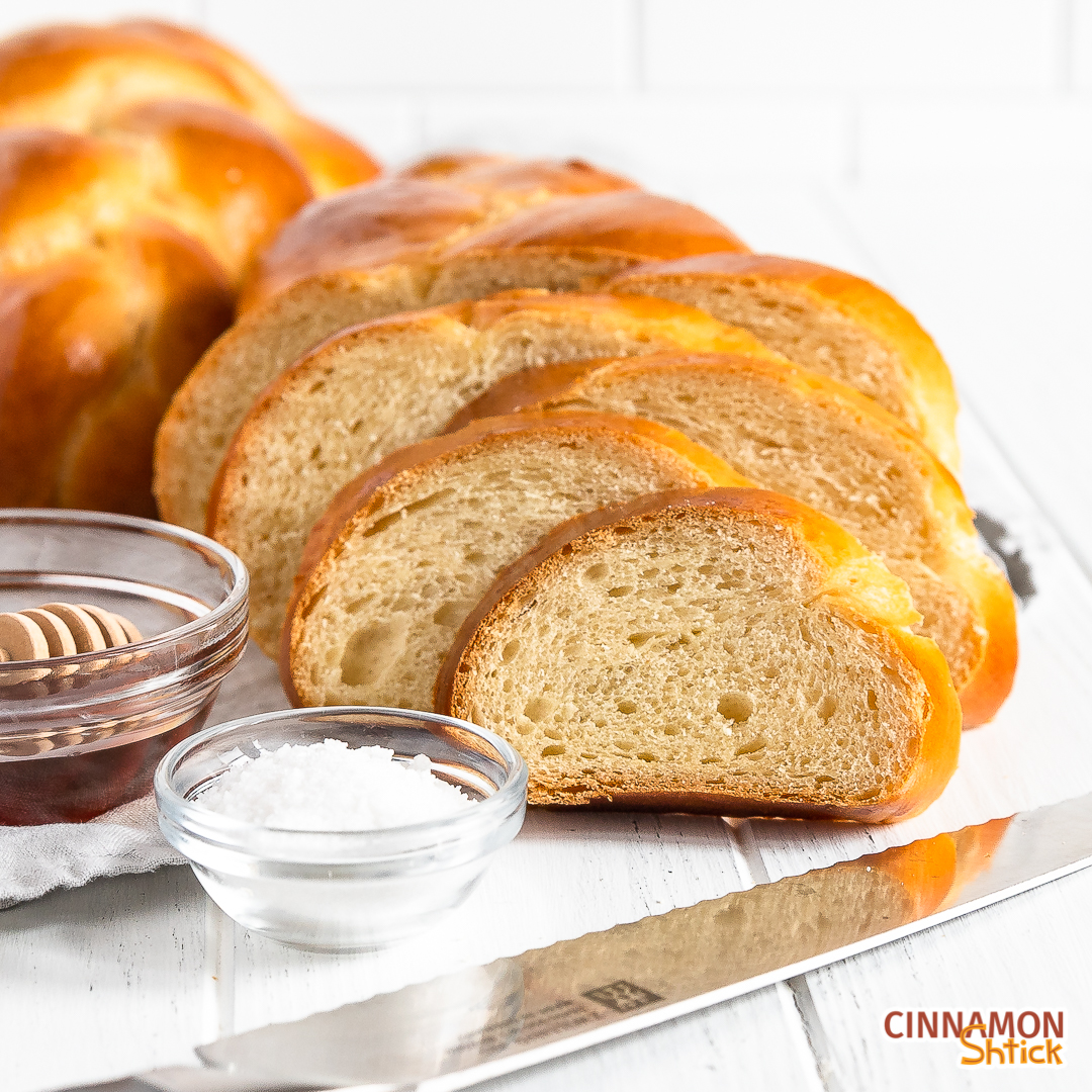 straight on shot of slices of challah with a small bowl of salt and a bowl of honey and a bread knife in forefront