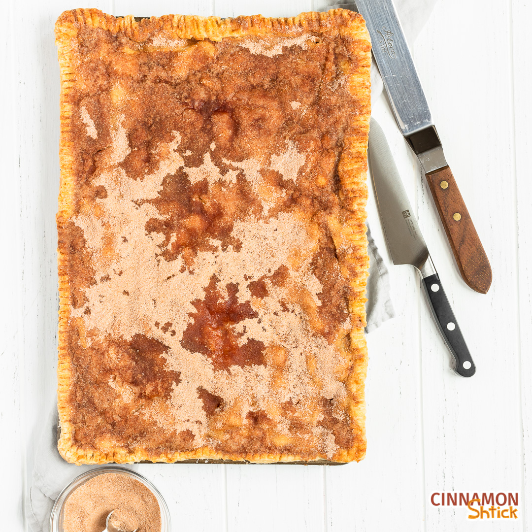 overhead view of apple slab pie with bowl of cinnamon sugar in lower left corner and knife and spatula in upper right corner